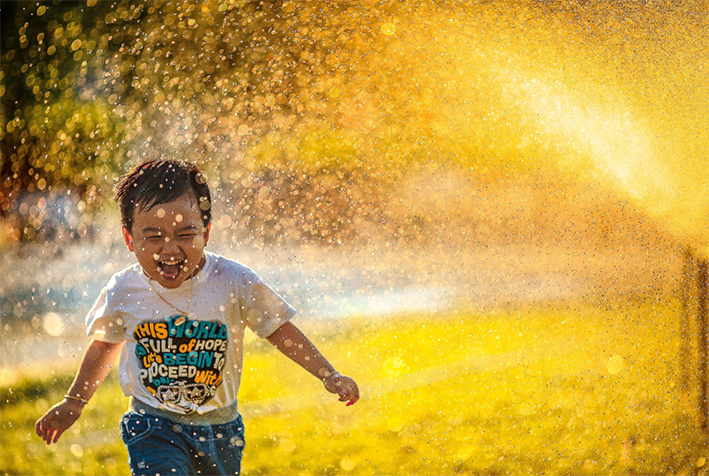 young boy running through water